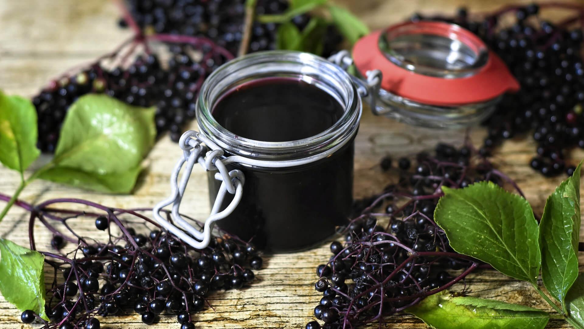 Elderberries and jar of elderberry syrup